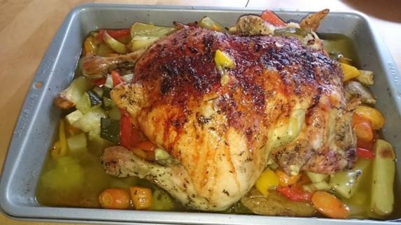 Helstekt Stange-kylling på en seng av grønnsaker